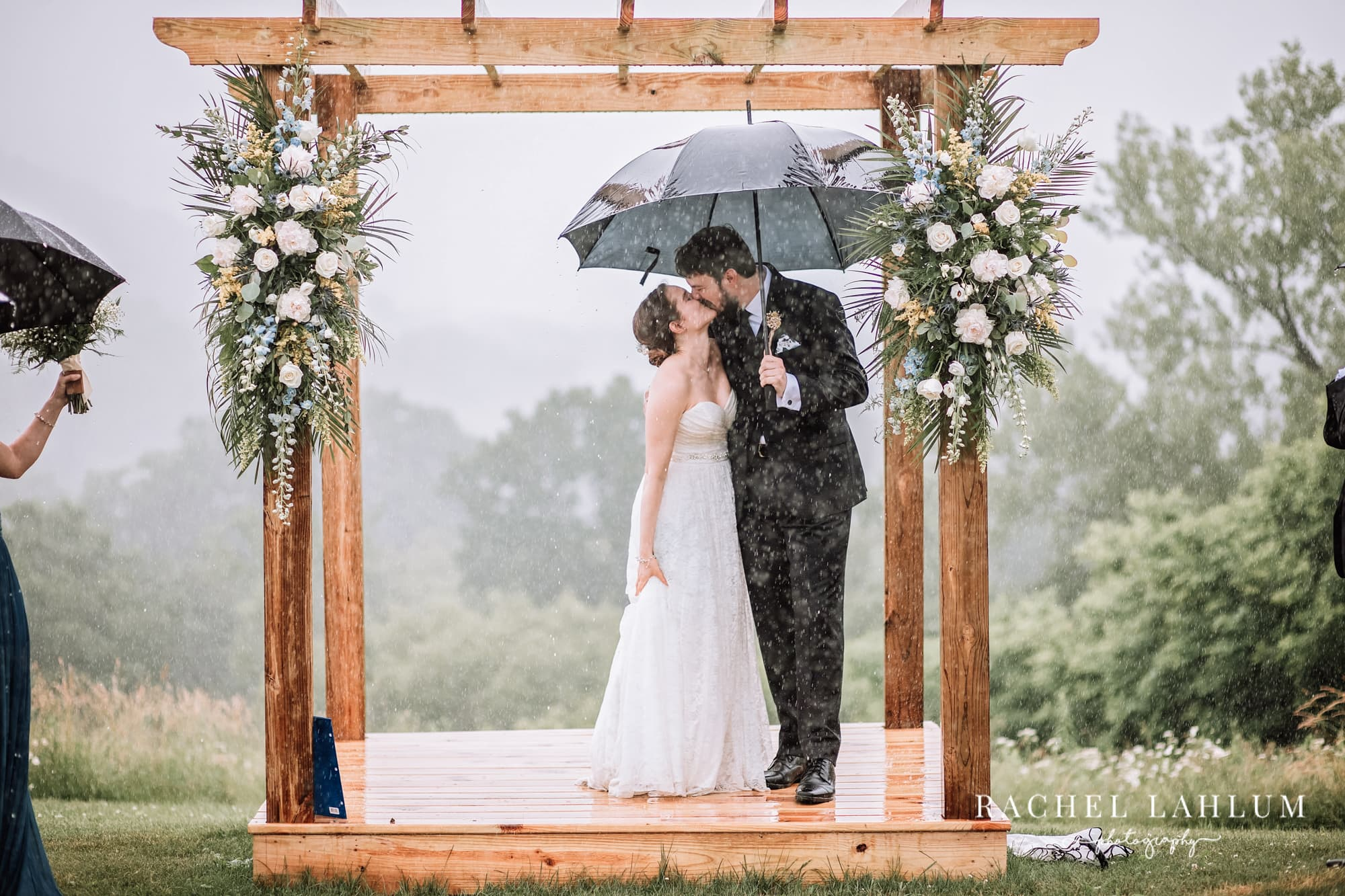 Bride and Groom kiss in the rain after exchanging vows at the Cedar Creek Barn Wedding Venue in Winona.