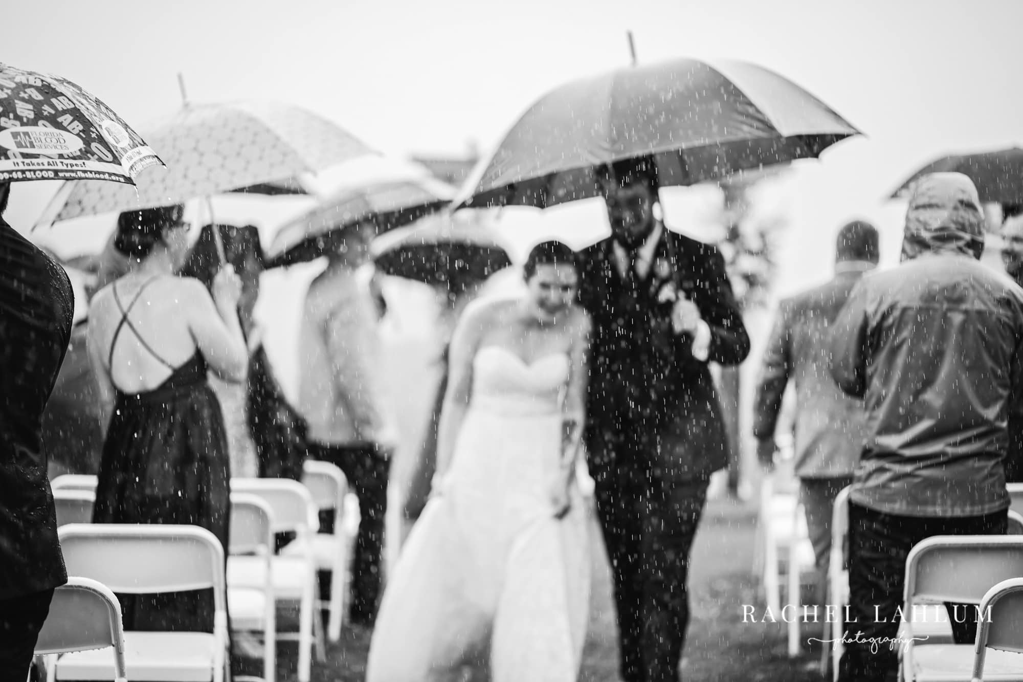 Black and white photo of newly wed couple walking down aisle in the rain.