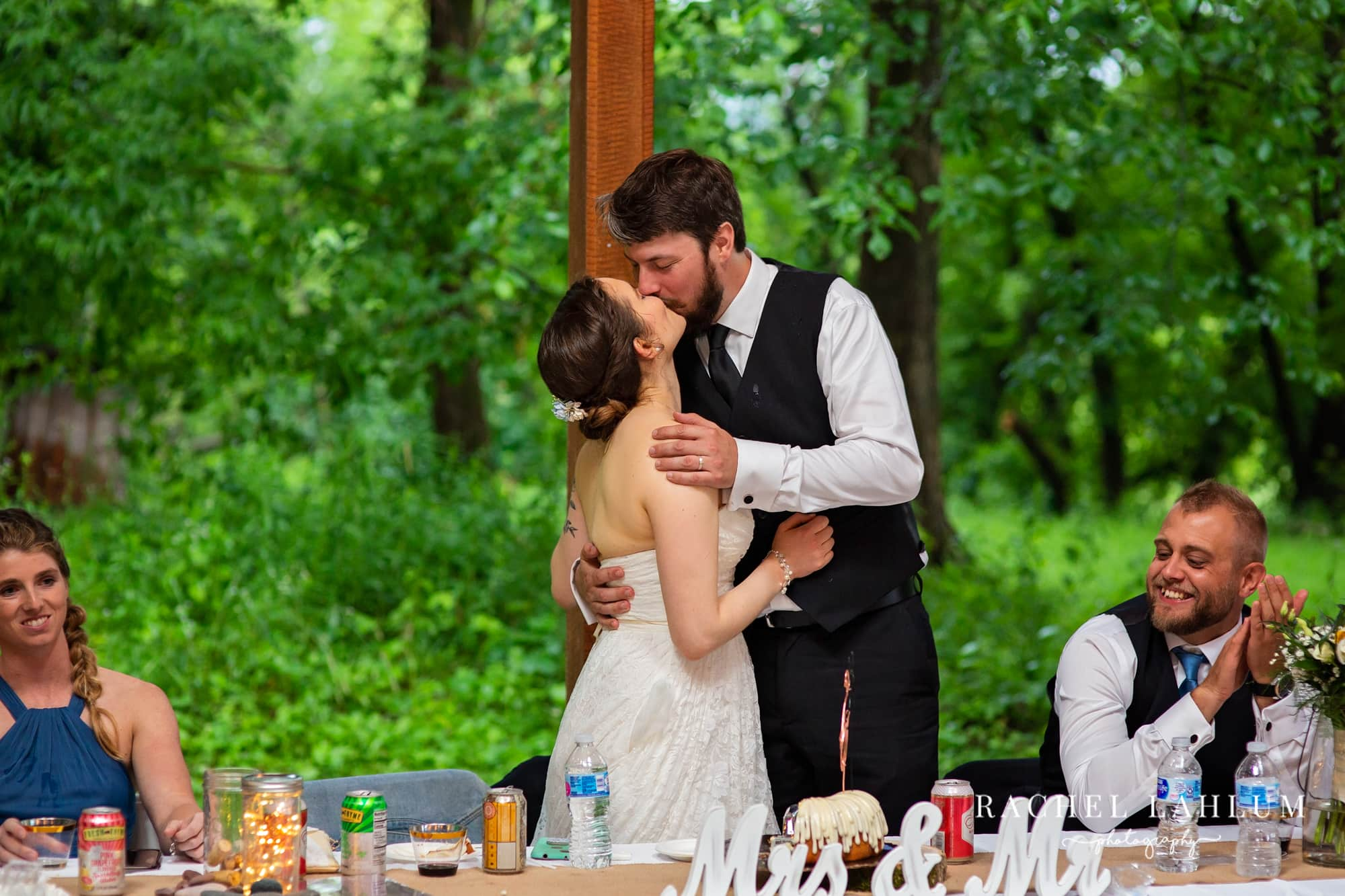 Newly wed couple kiss at during reception at Cedar Creek Barn in Winona, Minnesota.
