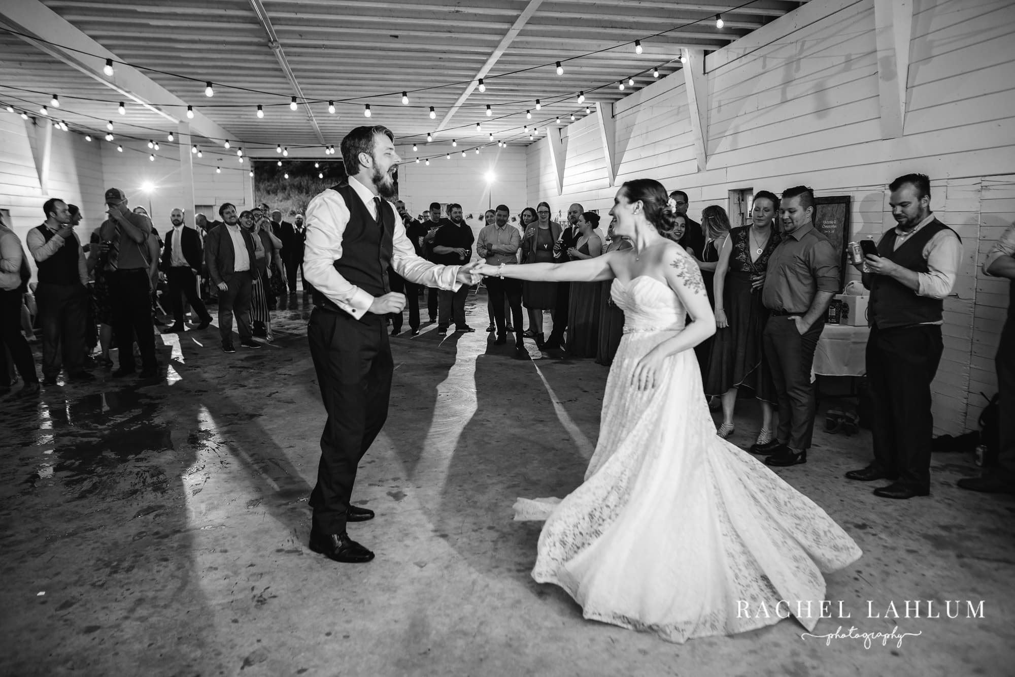 Black and white wedding photo of bride and groom sharing first dance at Cedar Creek Barn.