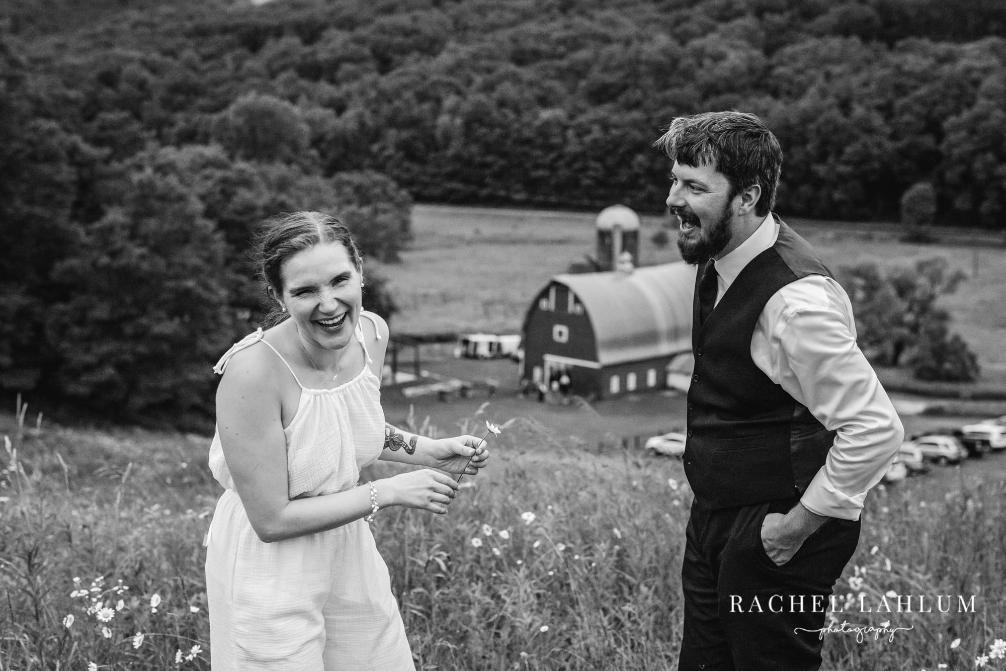Bride and groom laugh on top of a hill at Cedar Creek Barn.