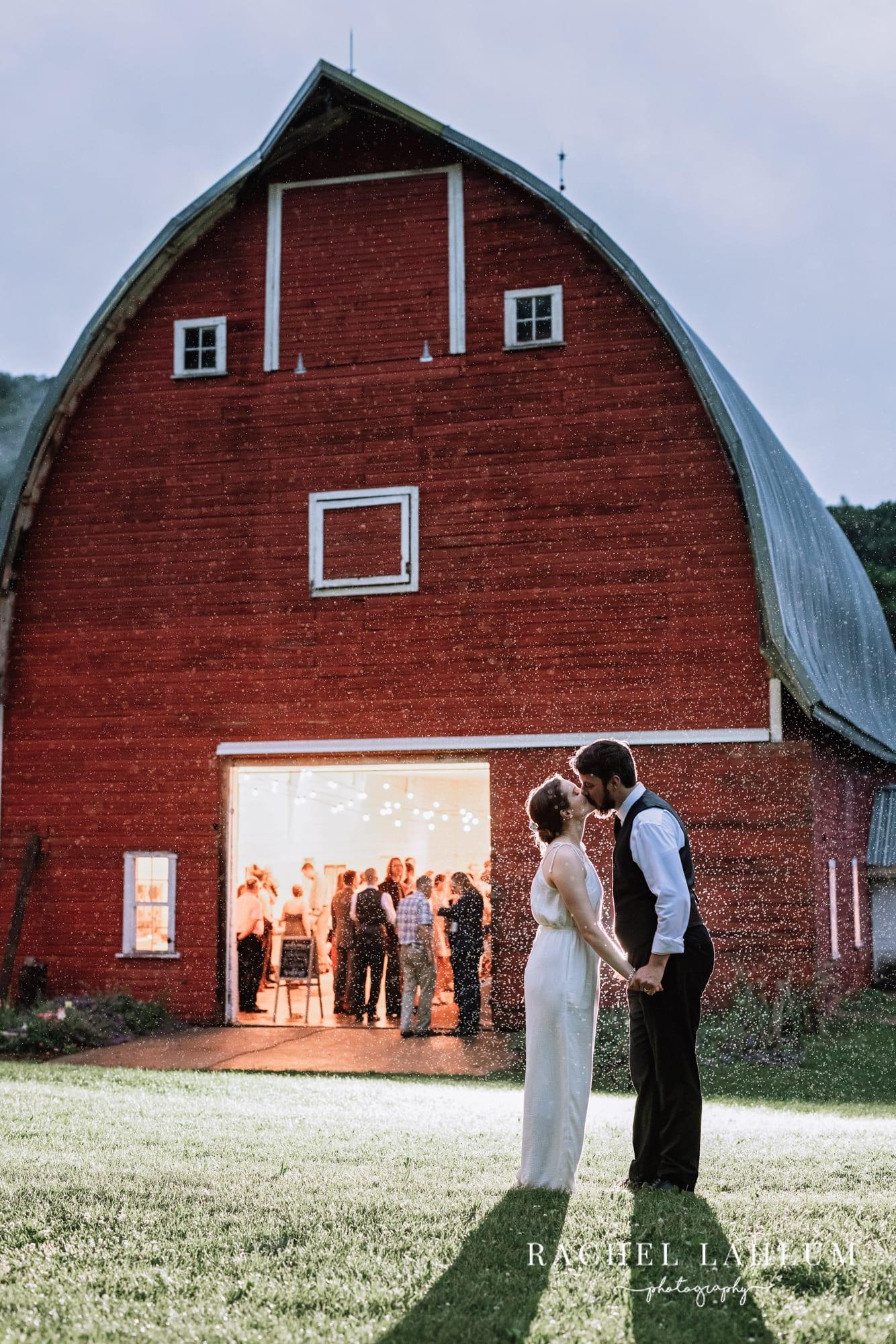 Bride and groom kiss in the rain outside of Cedar Creek Barn wedding venue in Winona, Minnesota.