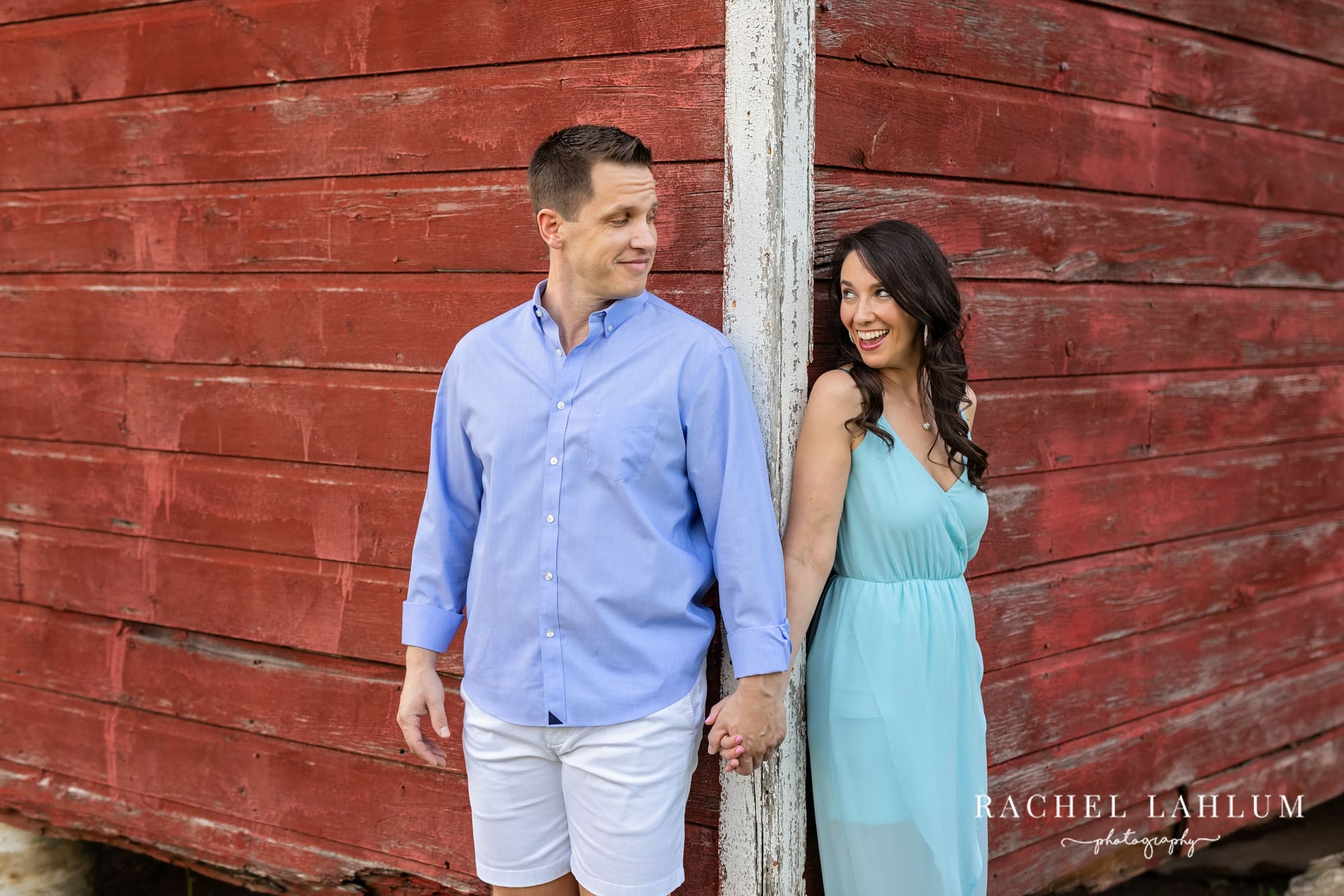 Couple glance at each other around the corner of a barn during engagement photography session at Henry's Woods.