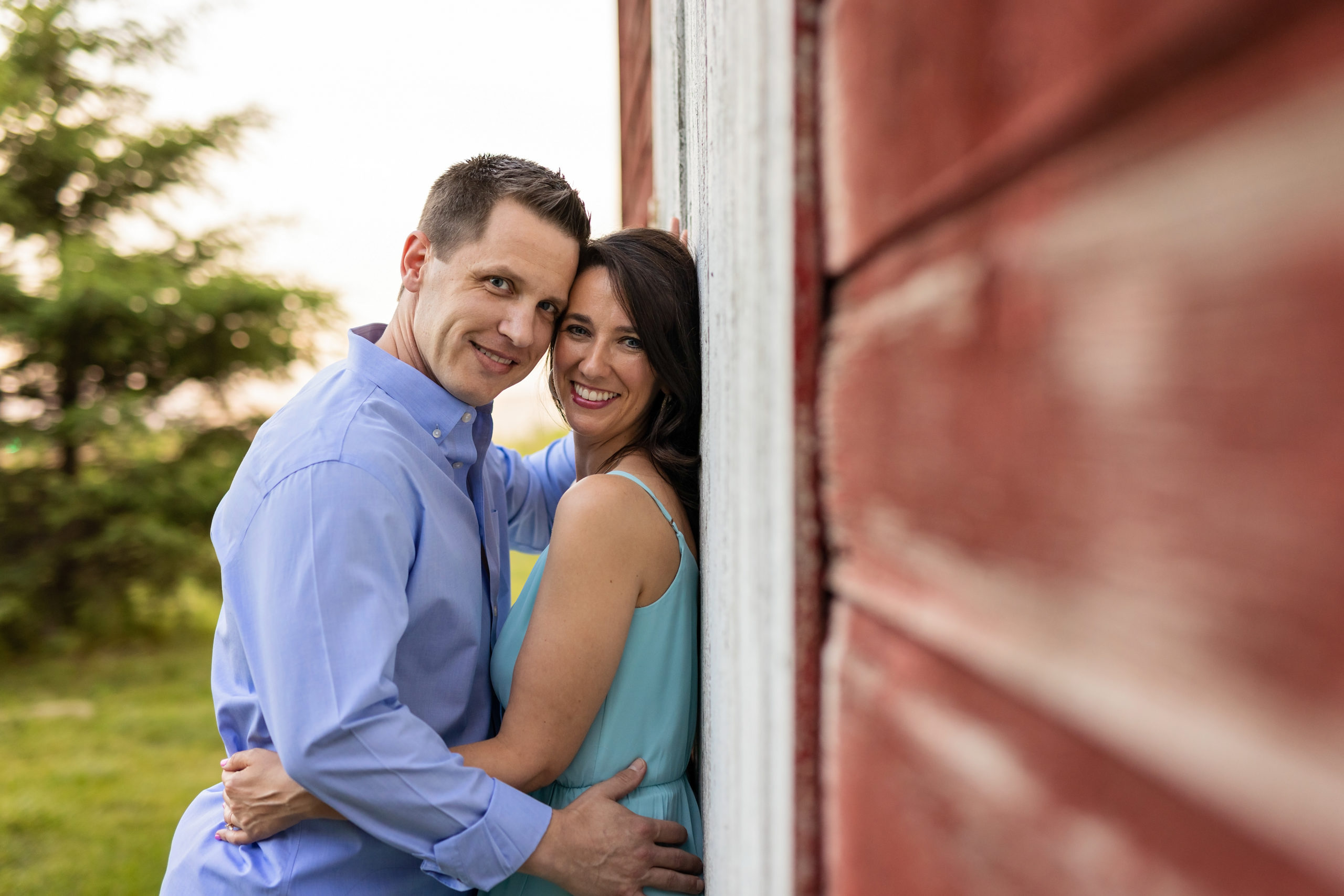 Couple pose alongside barn during engagement photography session at Henry's Woods.