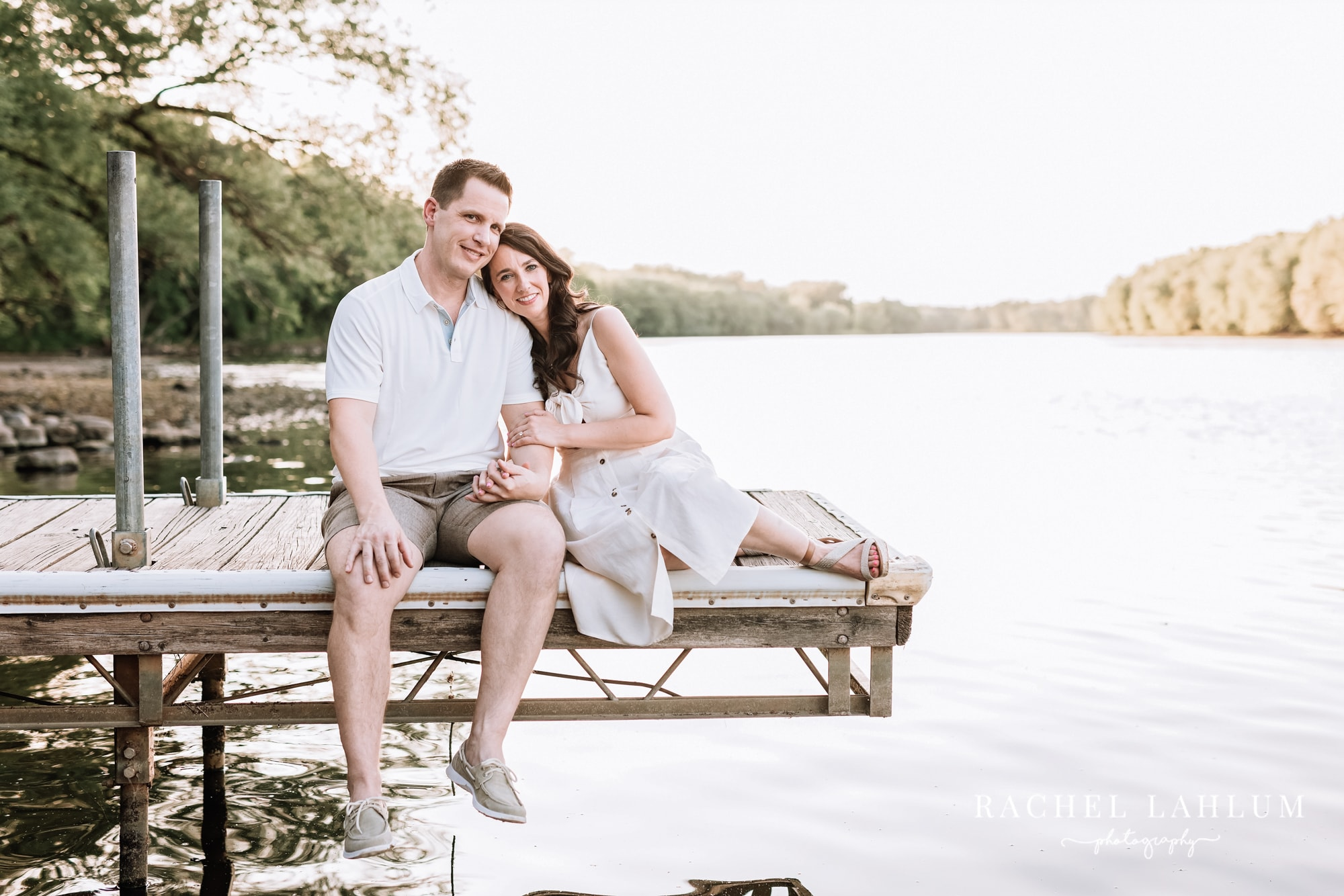 Newly engaged couple relax on a dock at Montissippi Park.