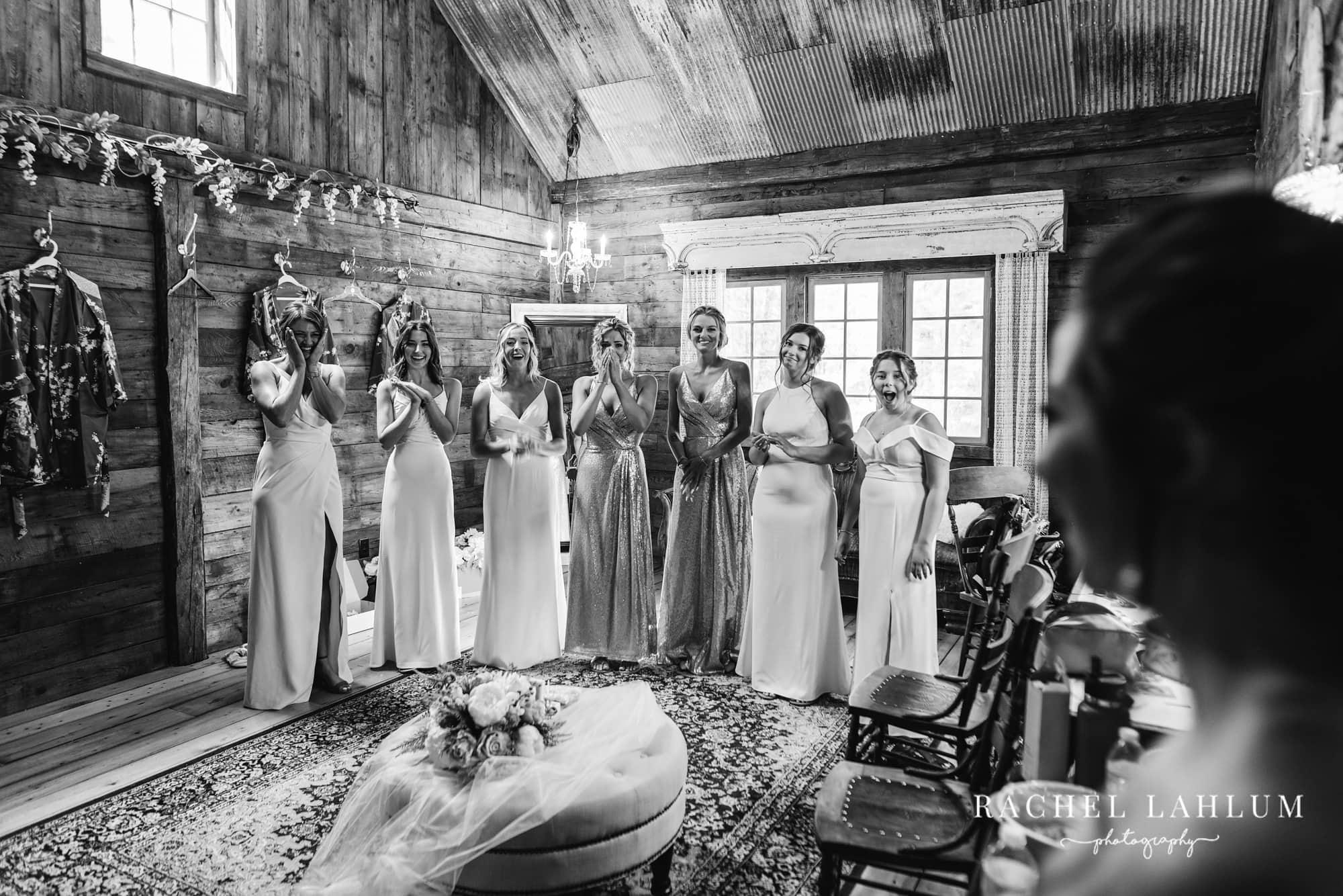 Bridesmaids watch bride enter bridal suite at Wilderness Wedding Barn in Bigfork, Minnesota.