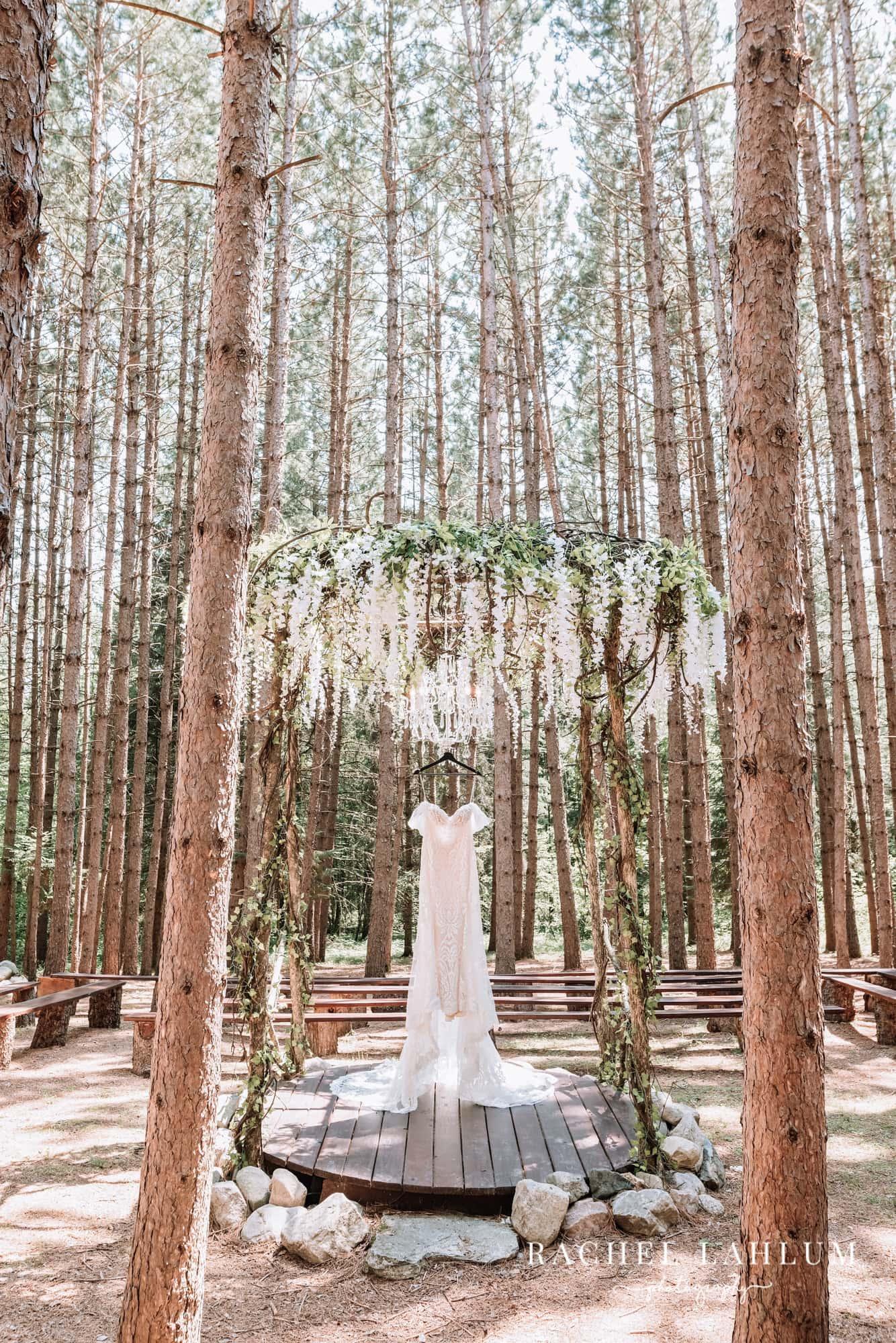 Wedding dress hangs from the ceremony gazebo among Norway pines at Wilderness Wedding Barn in Bigfork, Minnesota.