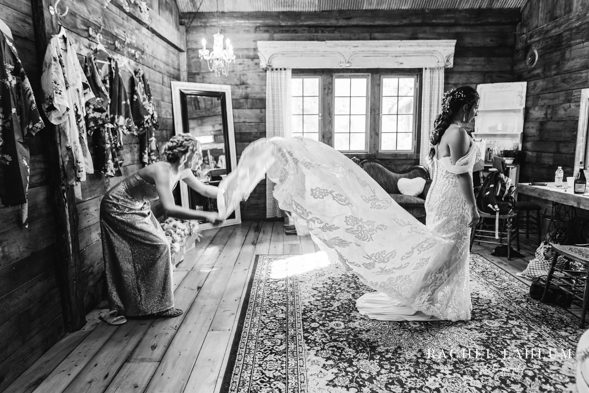 Bridesmaid straightens out wedding dress in bridal suite at Wilderness Wedding Barn.