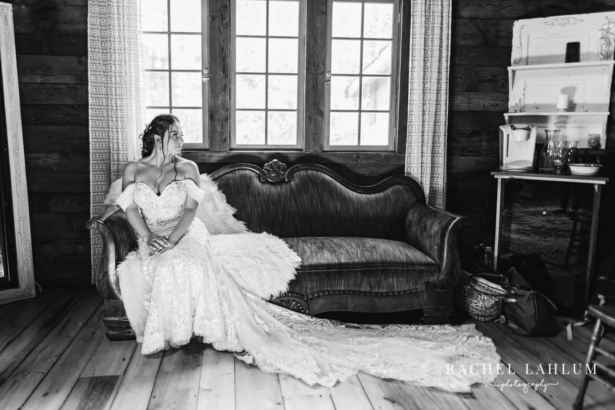 Bride sits on couch with wedding dress stretched out in bridal suite.