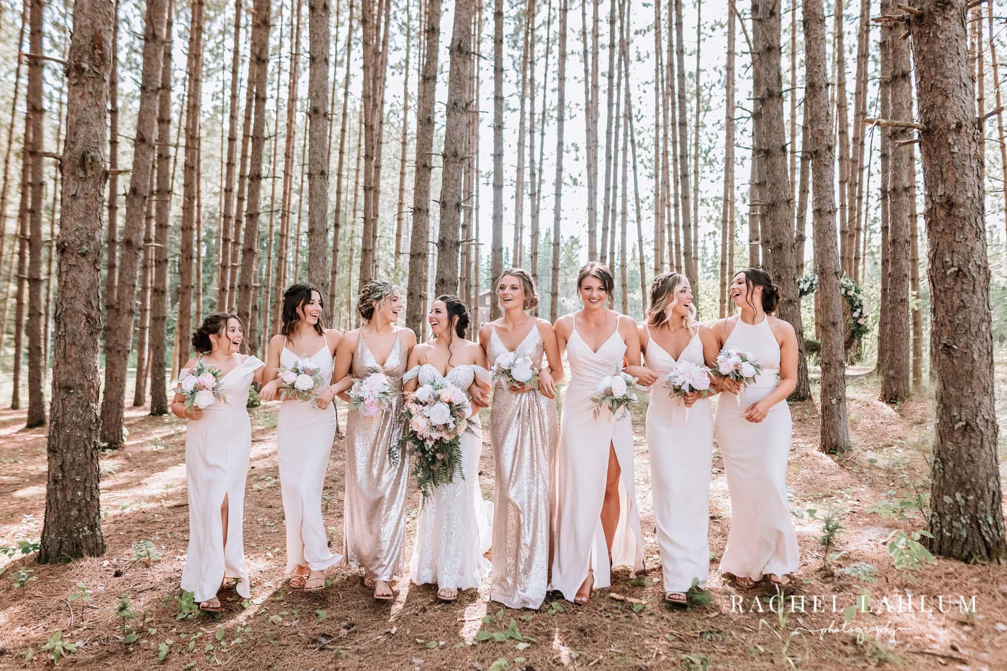 Bride and bridesmaids laugh and walk through the trees around Wilderness Wedding Barn in Bigfork, Minnesota.