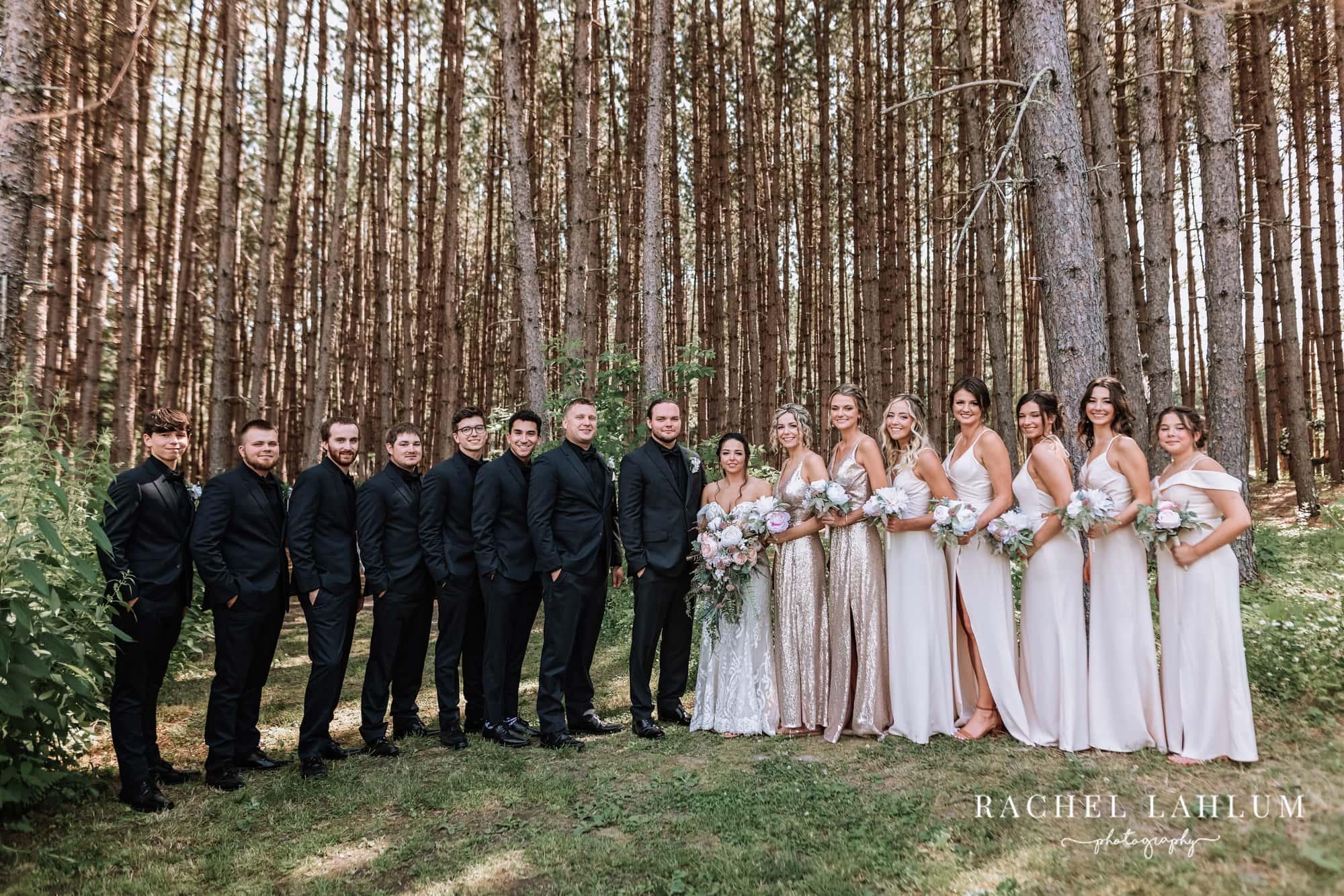 Bride, bridesmaids, groom and groomsmen pose before Olivia and Carter's wedding.