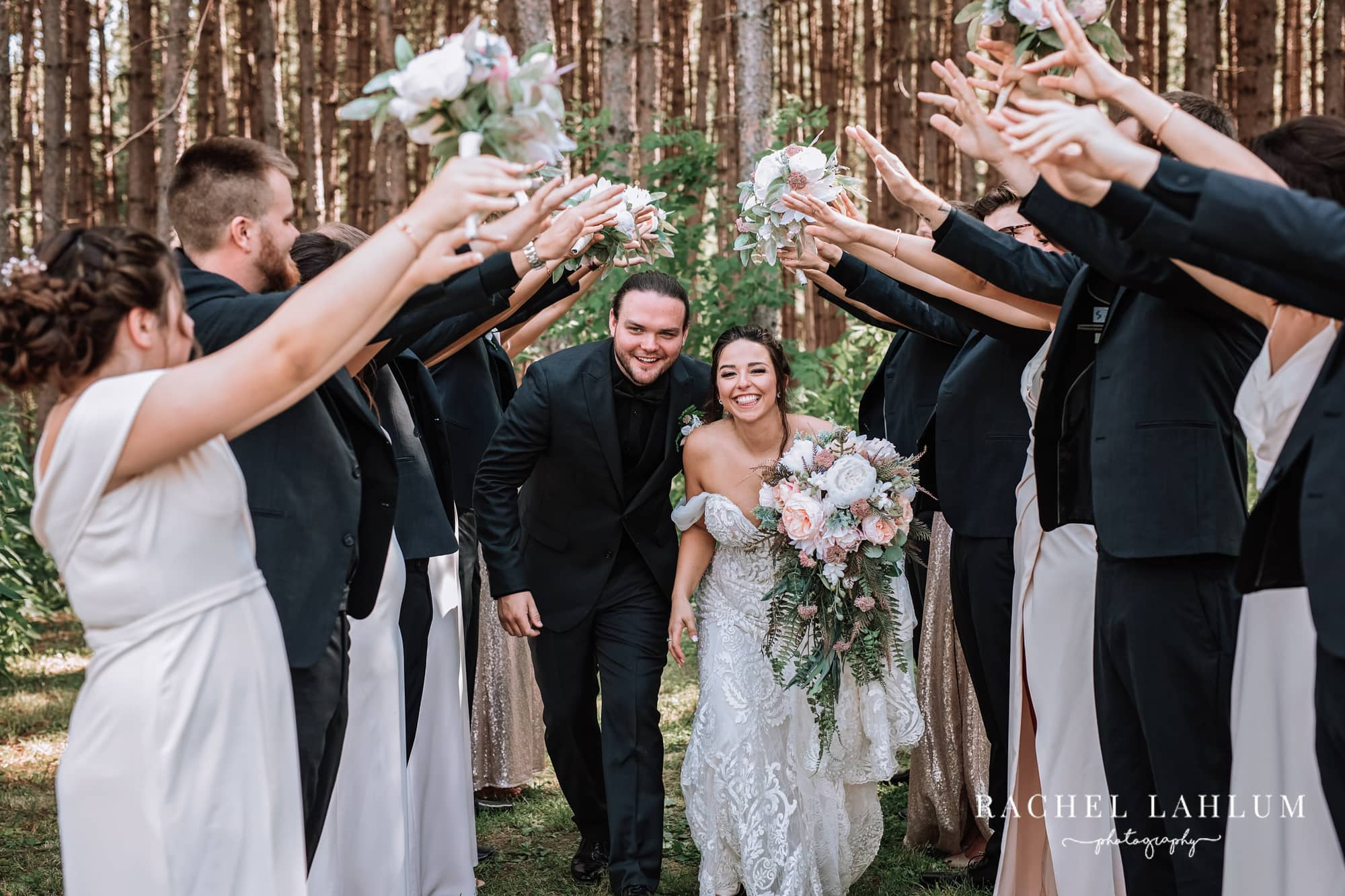 Bride and groom walk through a tunnel of bridesmaids and groomsmen at the Wilderness Wedding Barn in Bigfork, Minnesota.