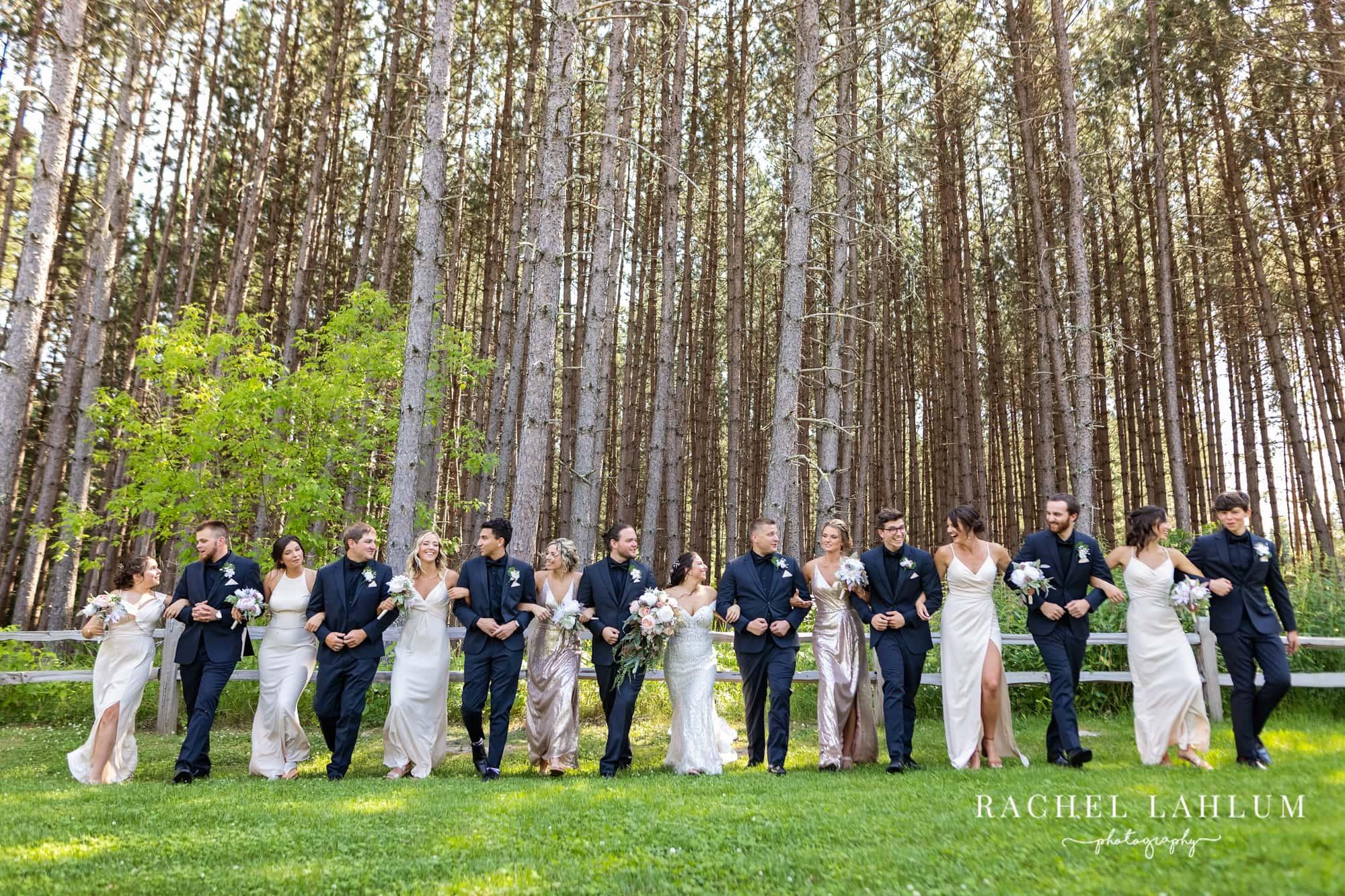 Bride, groom, groomsmen, and bridesmaids walk with arm in arm in field near Bigfork, Minnesota.