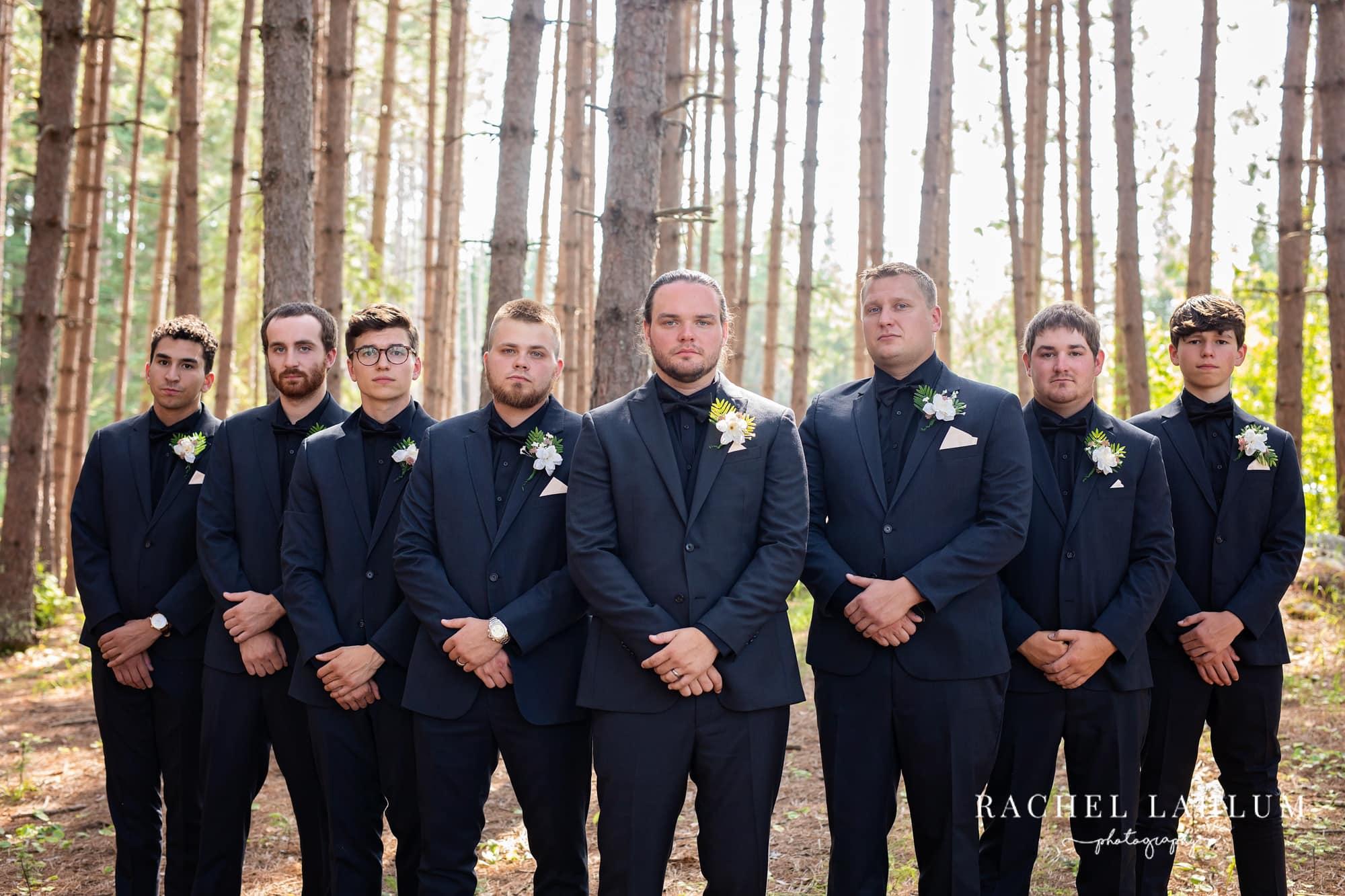 Groom and groomsmen pose before wedding in the woods at the Wilderness Wedding Barn in Bigfork, Minnesota.
