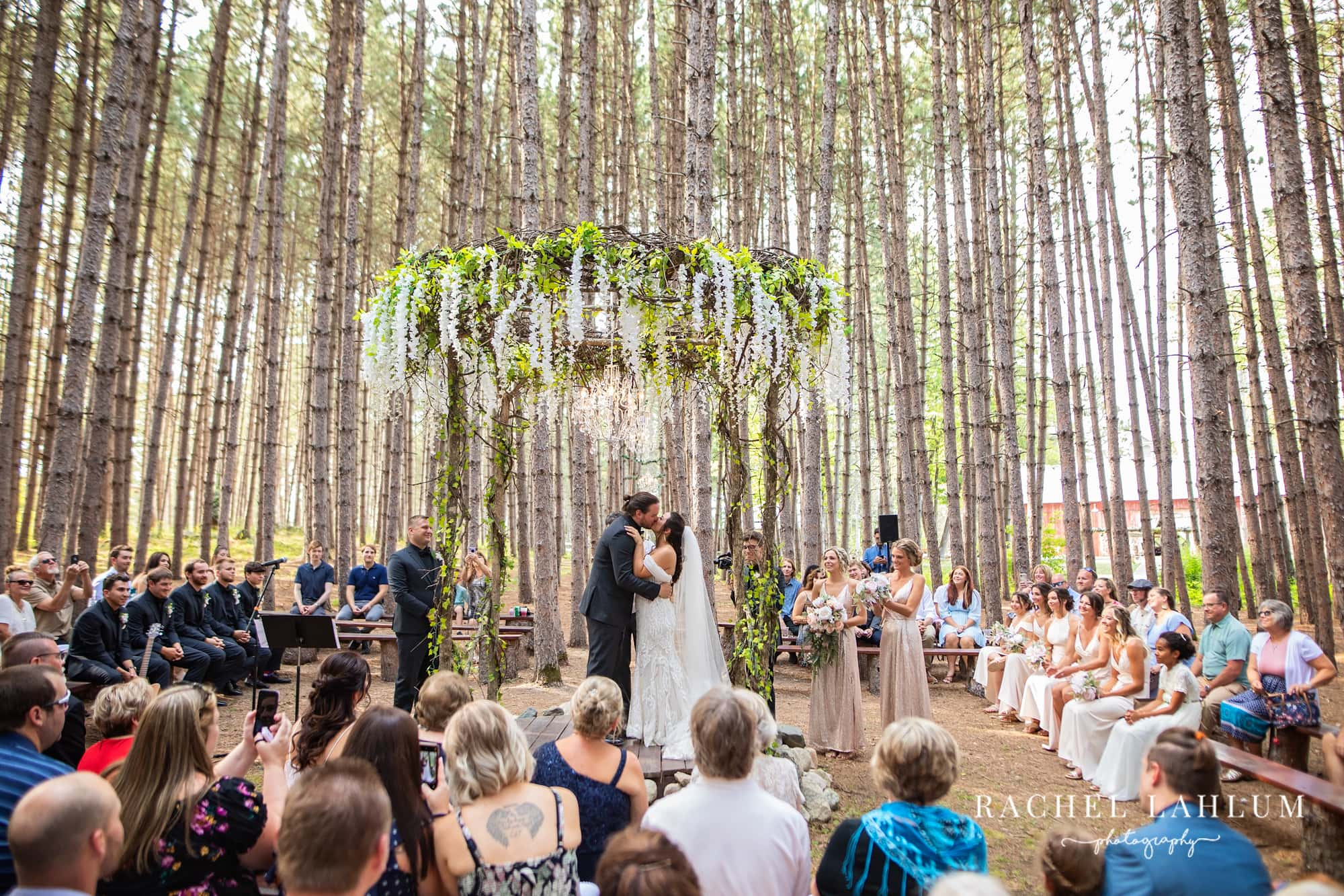 Bride and groom kiss as a married couple under gazebo at outdoor venue in Big Fork, Minnesota.