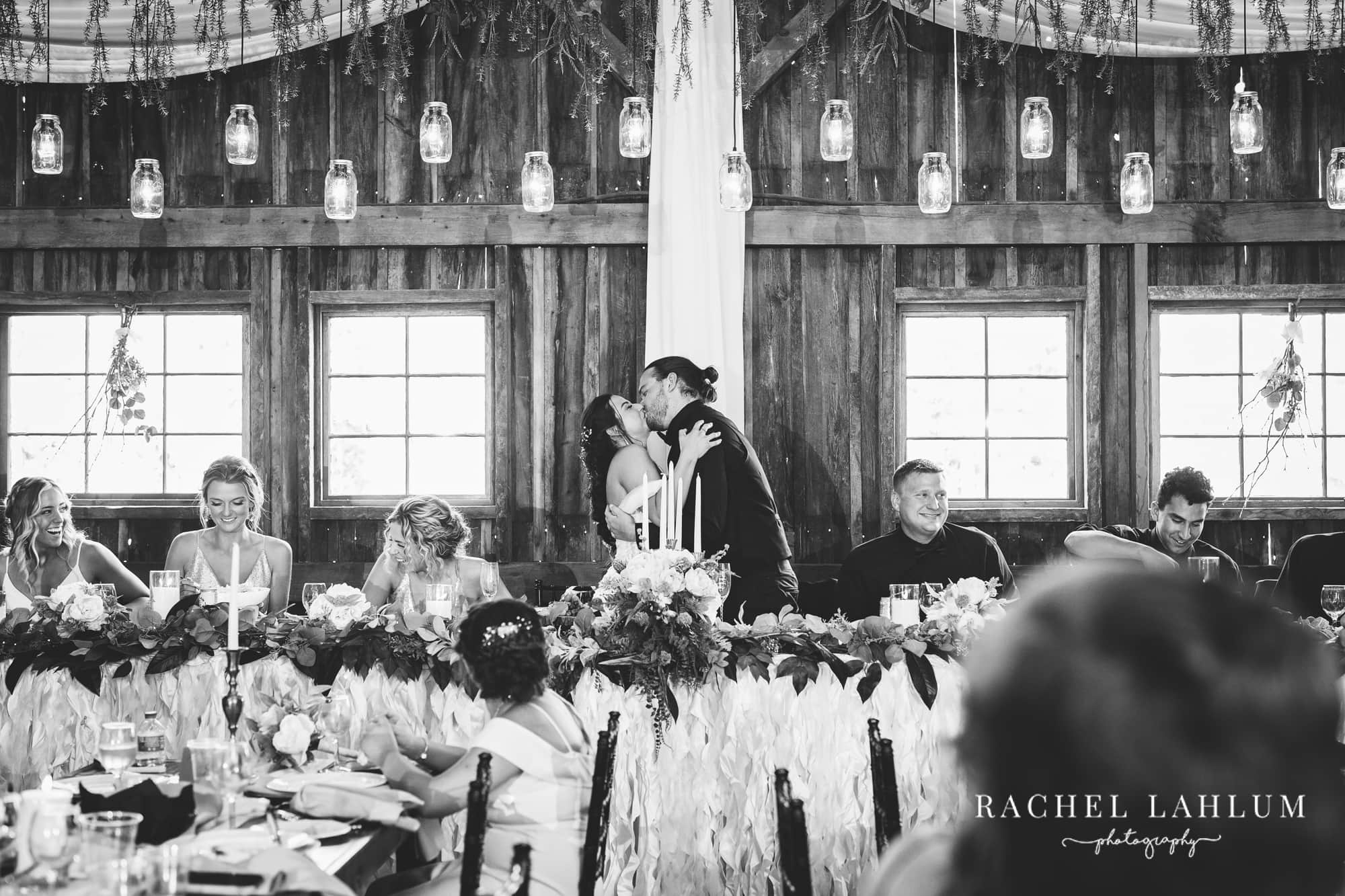 Bride and groom kiss during reception of wedding at Wilderness Wedding Barn in Bigfork, MN.