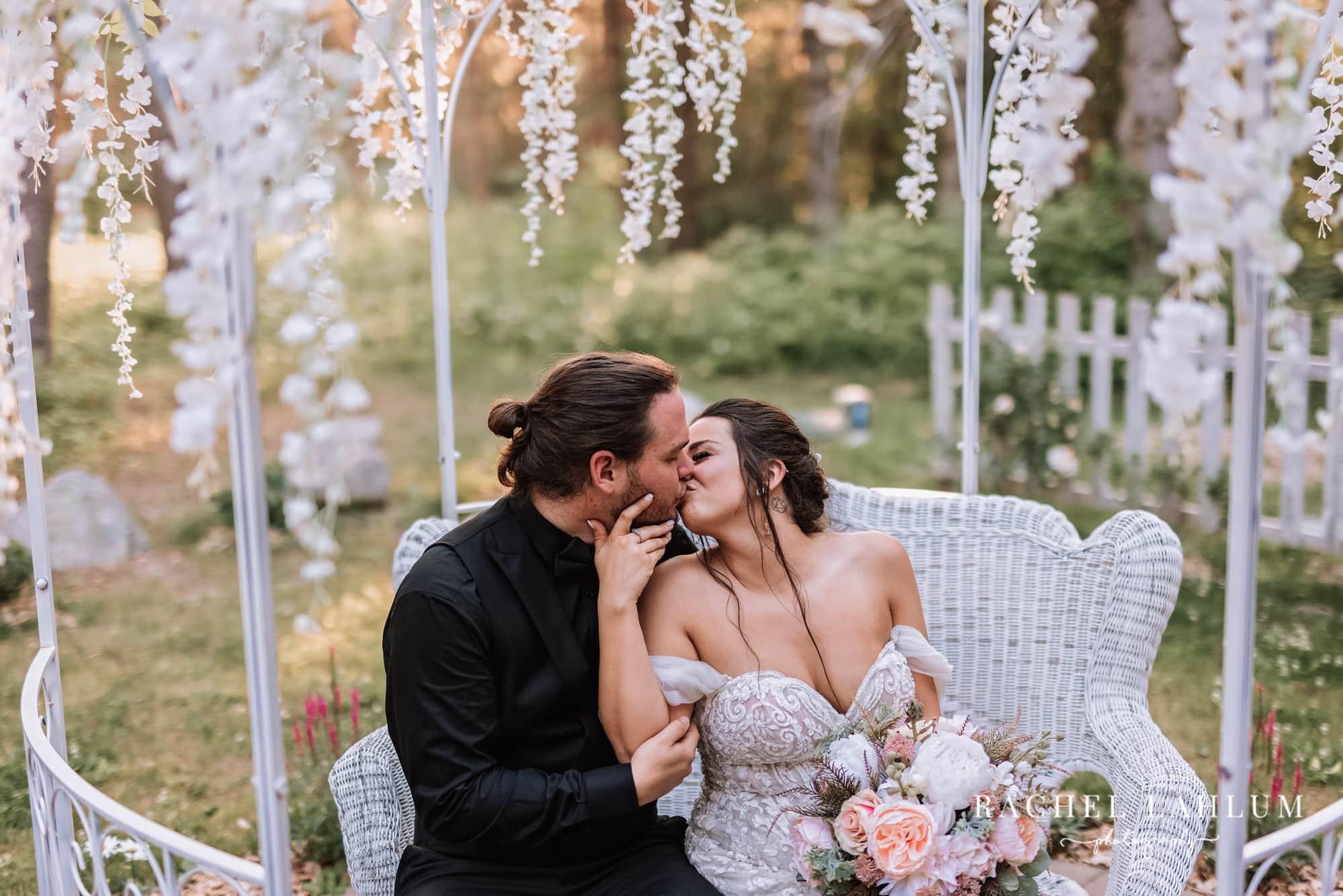 Bride and groom kiss at sunset after wedding at Wilderness Wedding Barn in Bigfork, Minnesota.