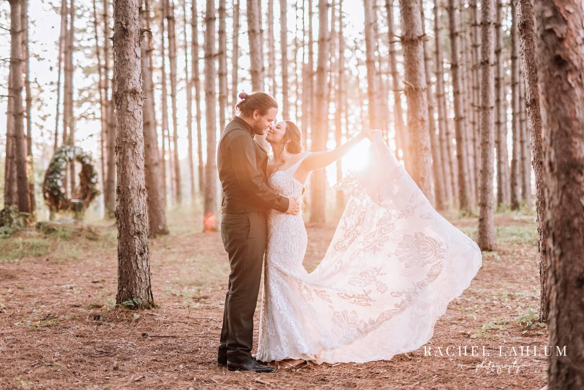 Bride twirls back of dress as she kisses groom in front of the sunset at Wilderness Wedding Barn in Bigfork, Minnesota.