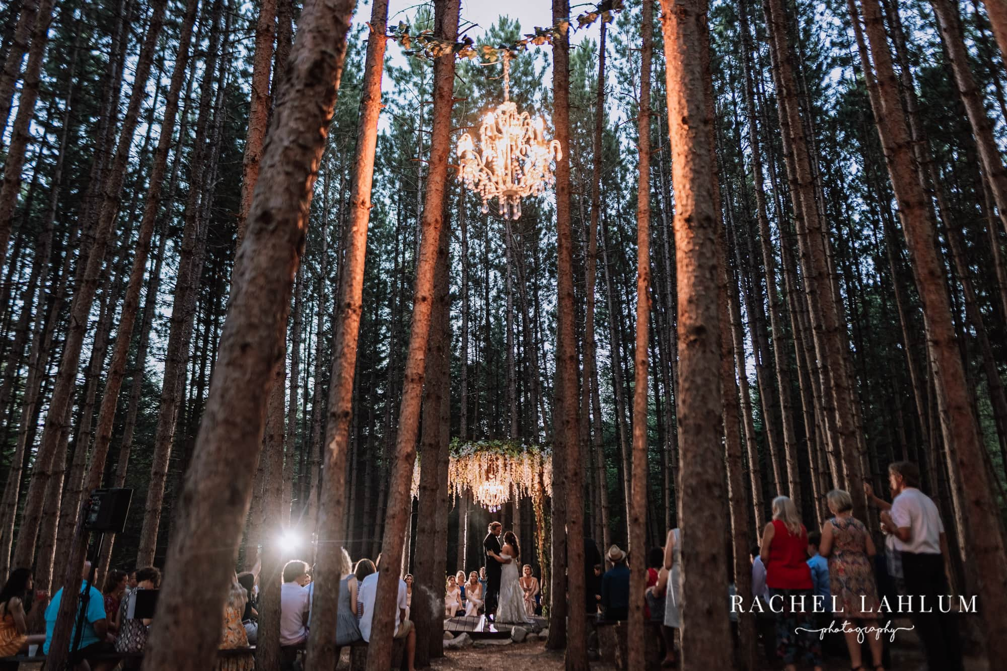 Bride and groom have first dance under outdoor chandelier in the woods after sunset.