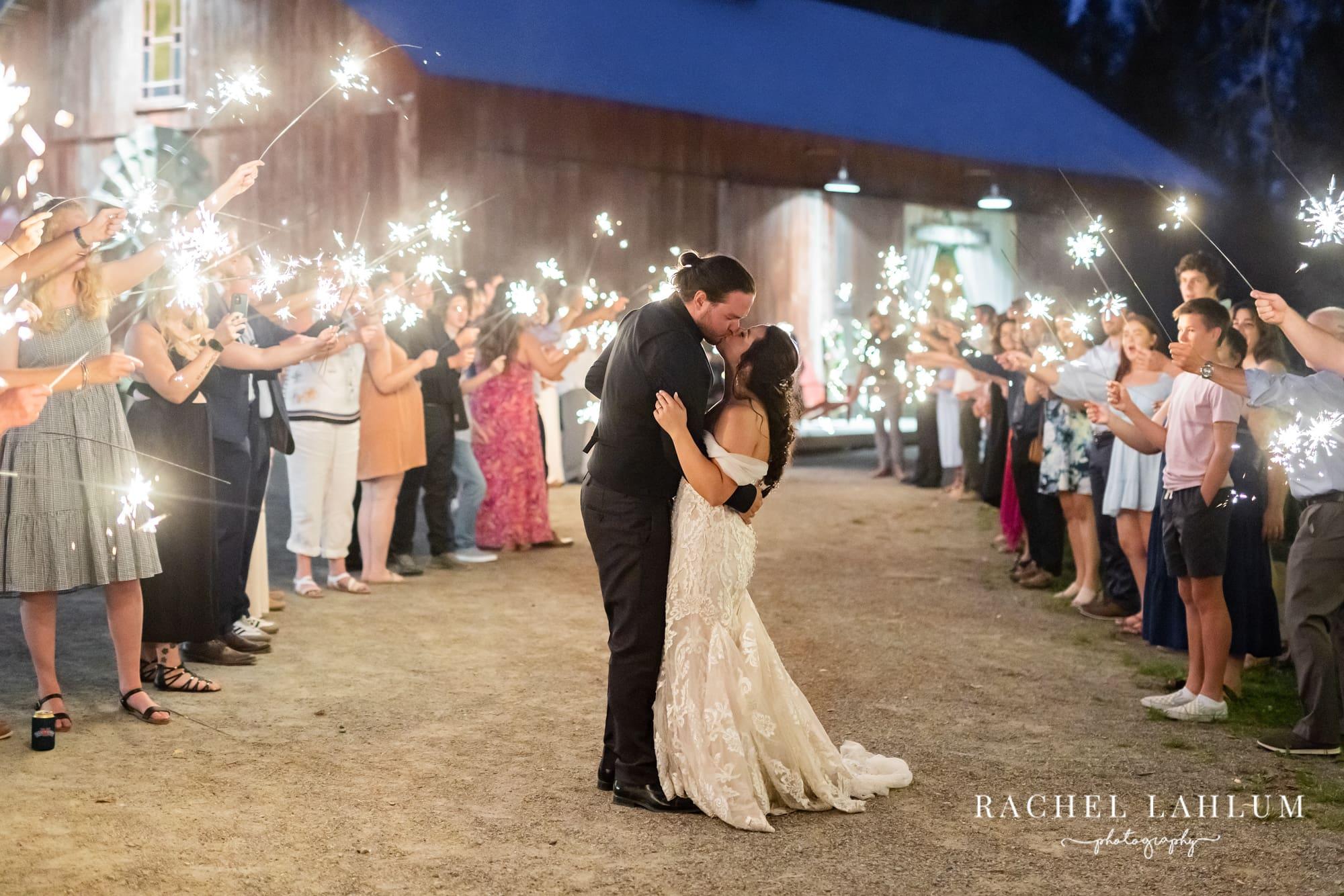 Bride and groom kiss in sparkler tunnel at Wilderness Wedding Barn in Bigfork, MN.
