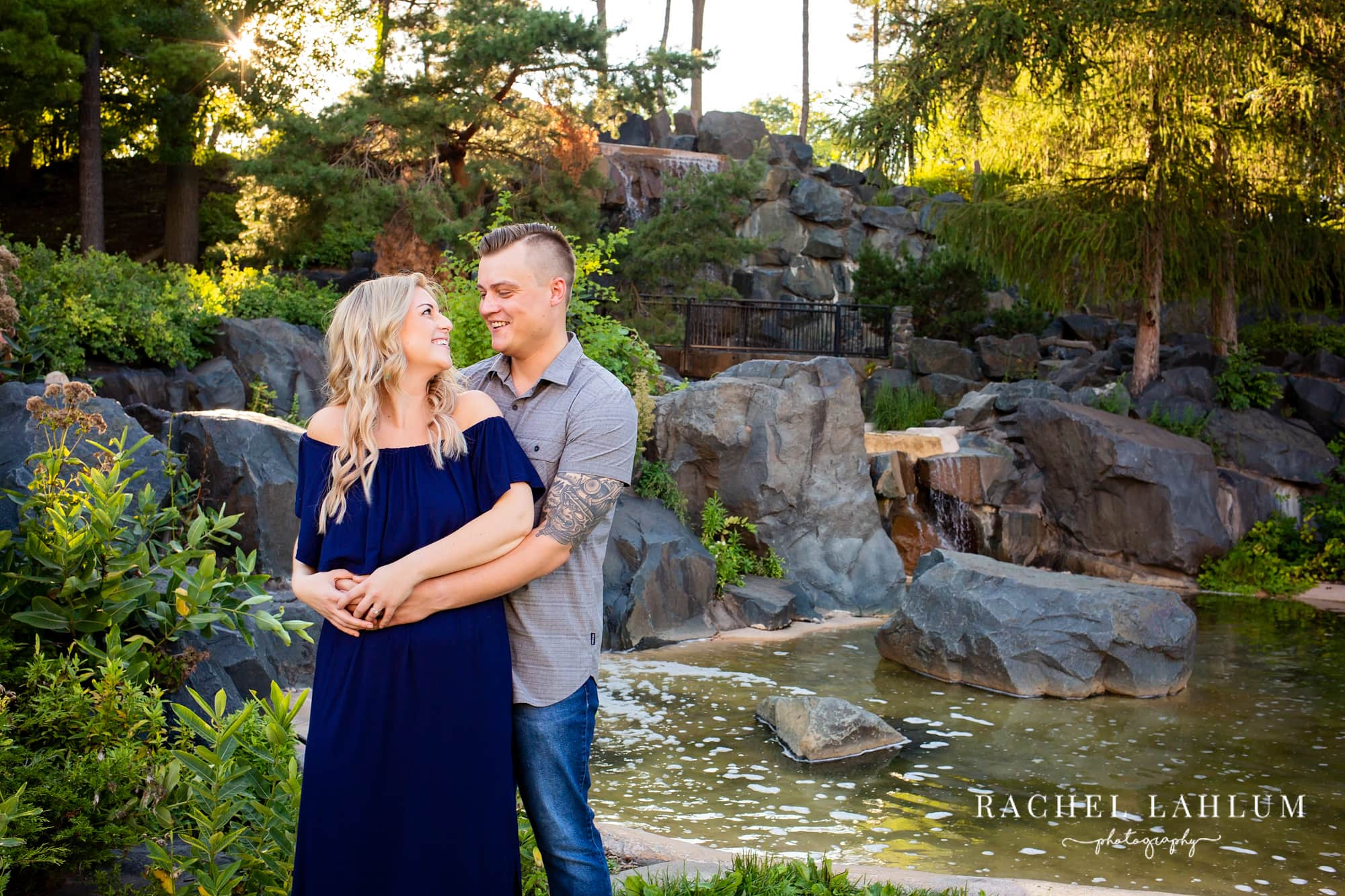 Engaged couple embrace at water feature at Como Park in St. Paul, Minnesota,