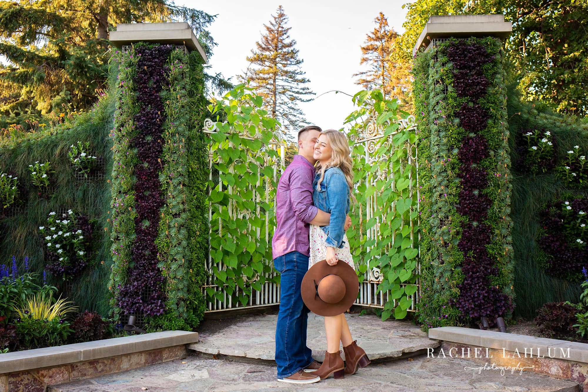 Engaged couple kiss in front of vine-covered gate at Como Park in St. Paul, Minnesota.