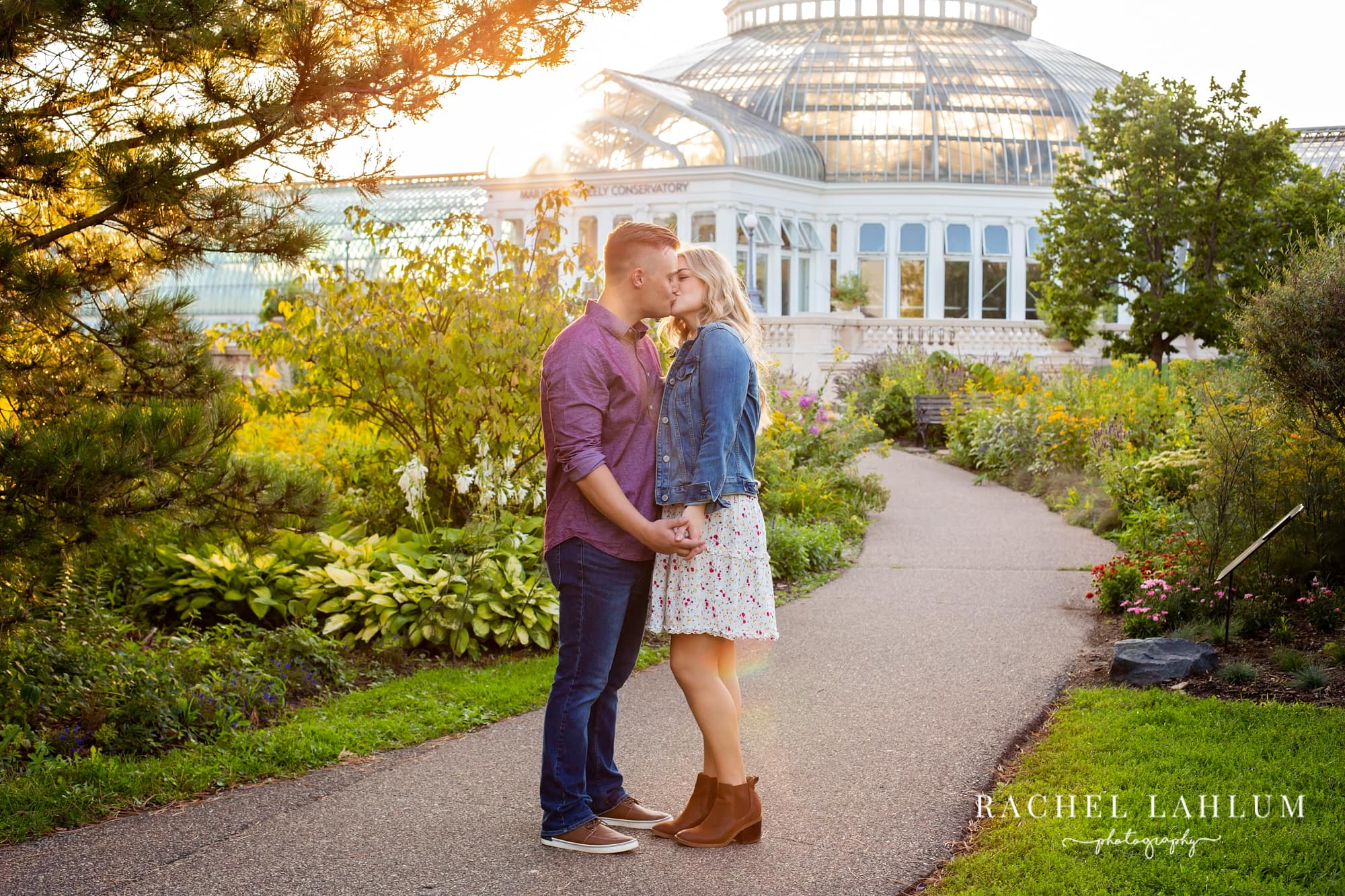 Tyler and Emily kiss during an engagement session in front of Como Conservatory.