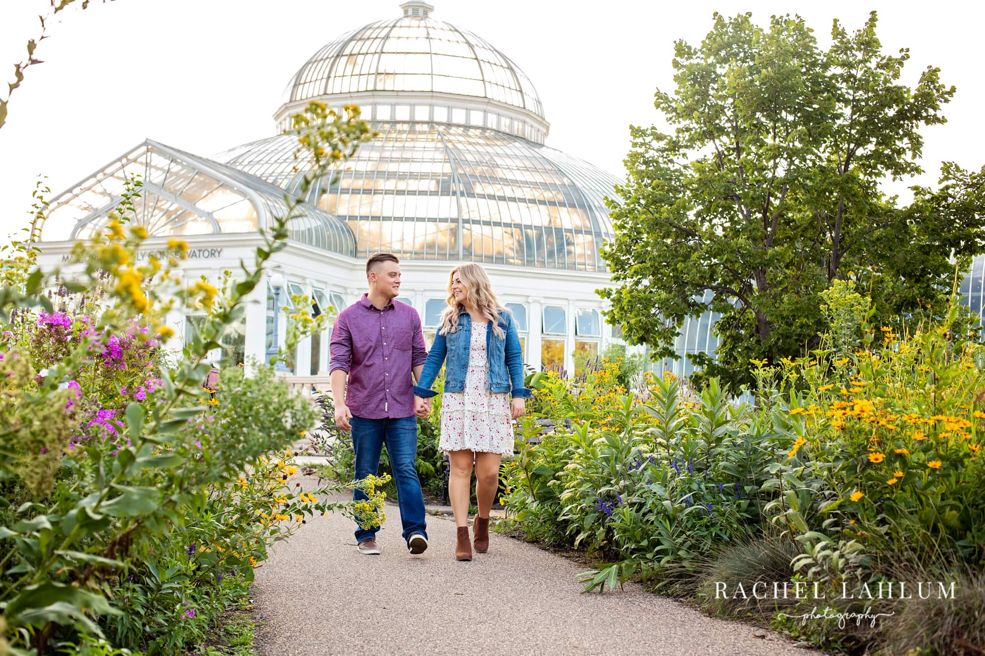 Engaged couple walk down trail in front of Como Conservatory.