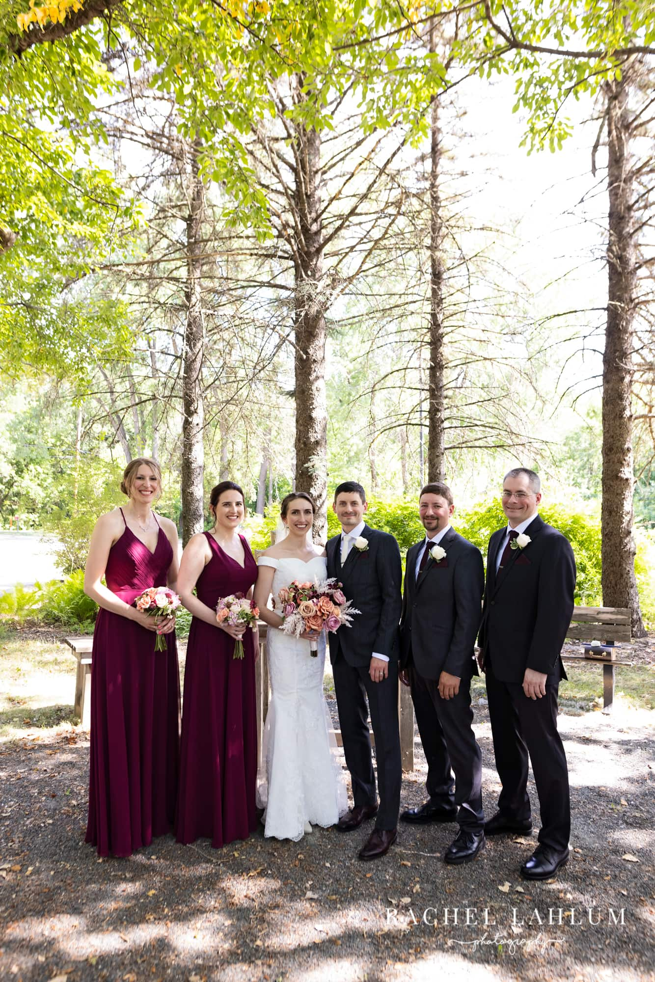 Wedding party pose for a photo under the trees after St. Paul wedding ceremony.