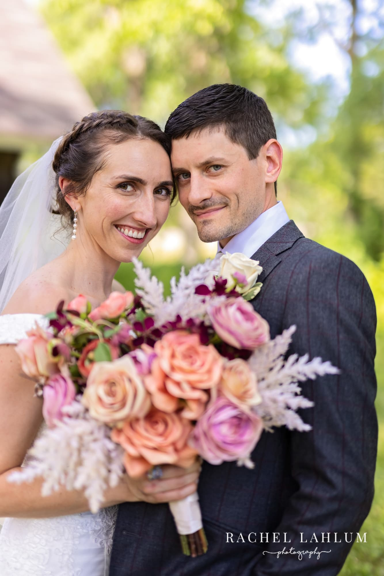 Bride and groom smile behind bouquet after wedding ceremony in St. Paul, MN.