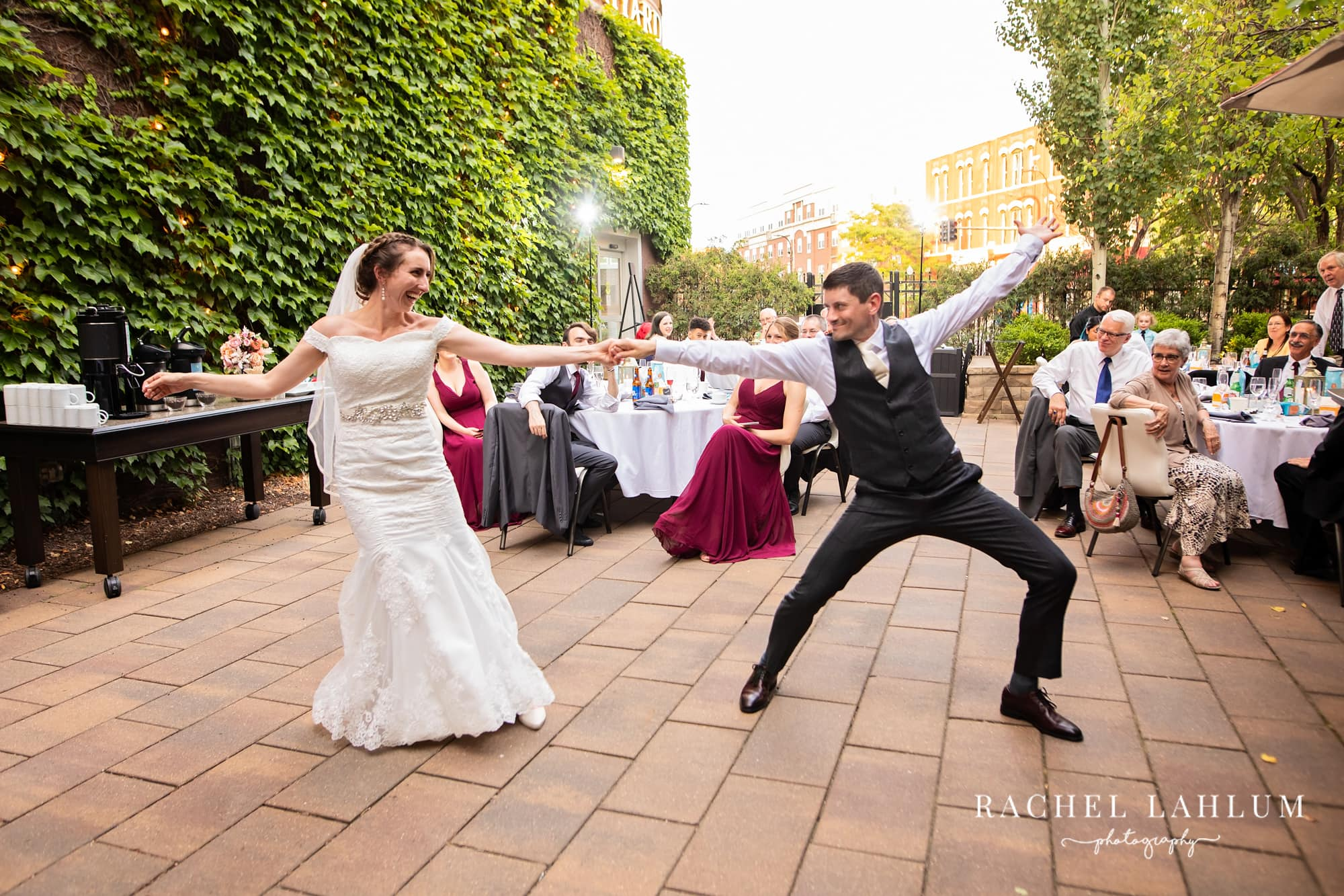 Bride and groom show off dance moves during first wedding dance at Courtyard by Marriot in Minneapolis, Minnesota.