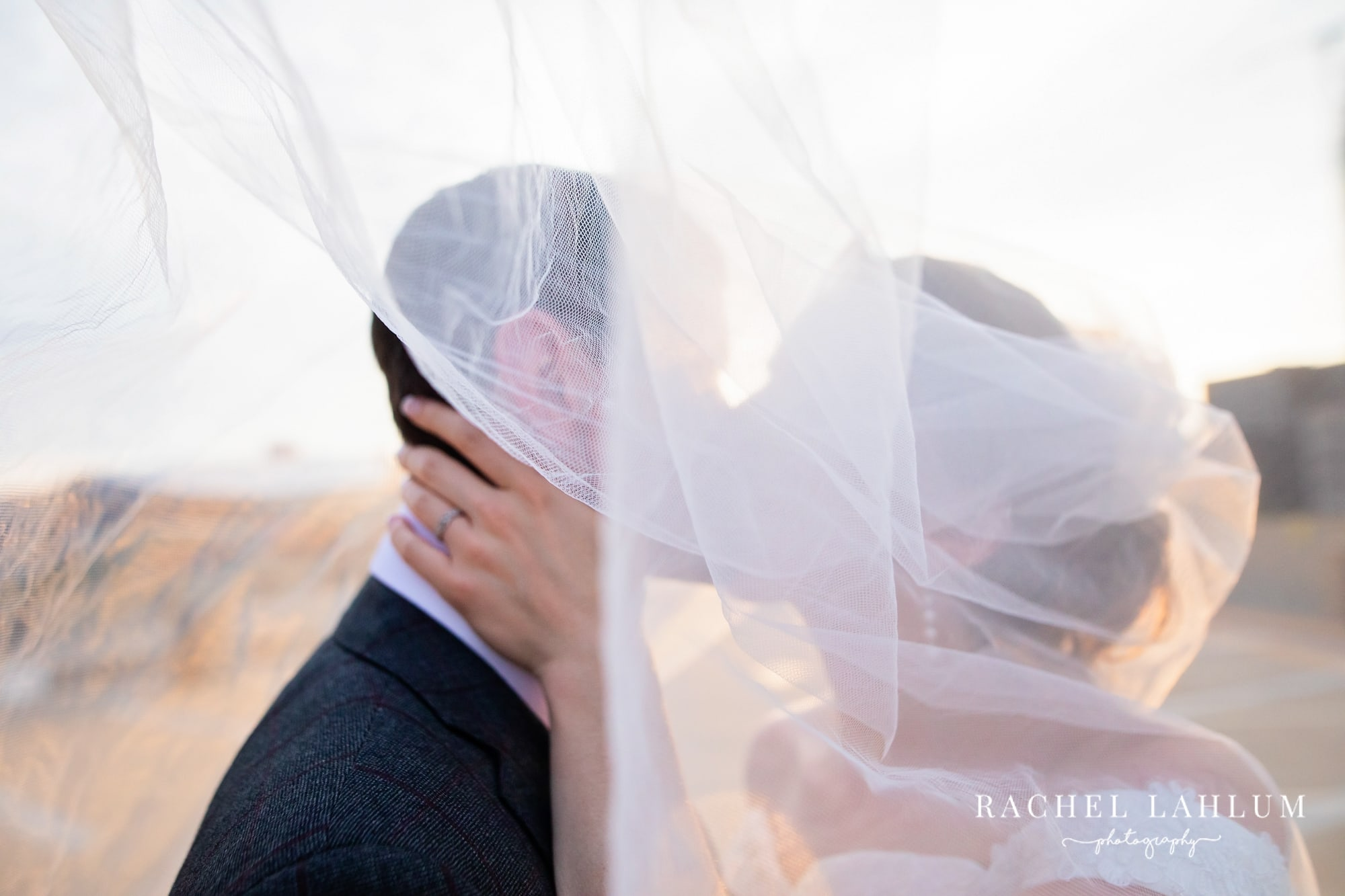 Newly weds kiss behind the bride's veil after Twin Cities wedding.